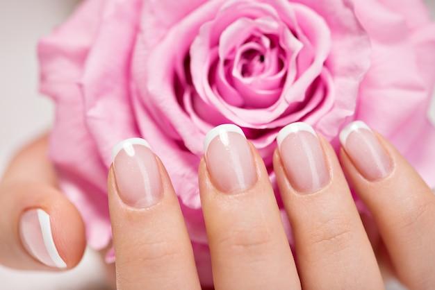 Lindas unhas de mulher com linda manicure francesa e rosa rosa Foto gratuita