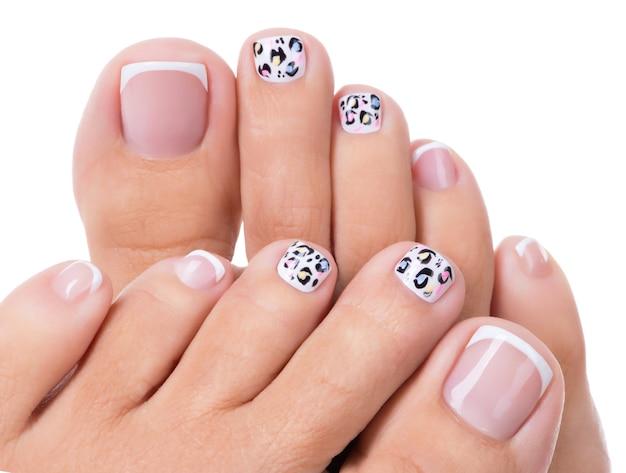 Lindas unhas femininas das pernas com bela manicure francesa e arte Foto gratuita