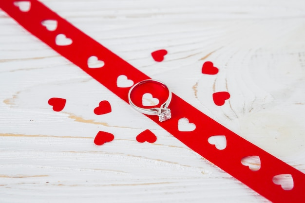Lindo anel na fita perto de corações de ornamento Foto gratuita