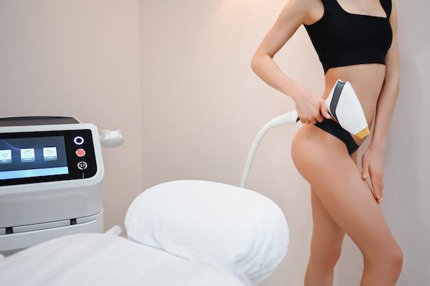 Lindo apto corpo de mulher com pele macia suave em lingerie preta com dispositivo de aparelho a laser isolado no salão de beleza. depilação e cosmetologia. conceito de spa de depilação. espaço livre para banner de texto Foto Premium