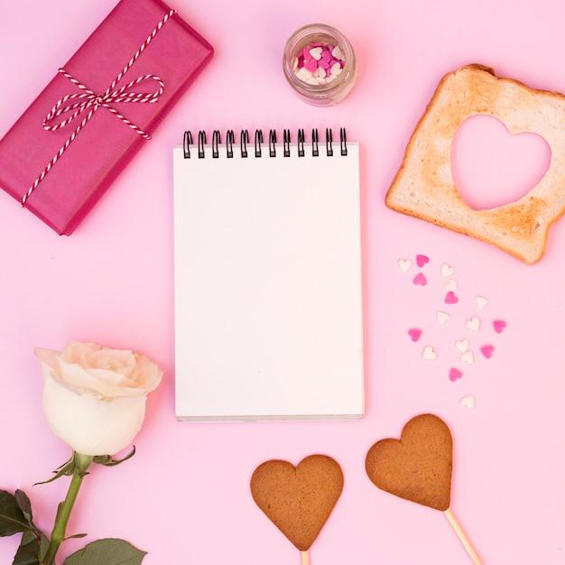 Lindo arranjo romântico do bloco de notas com cookies Foto gratuita
