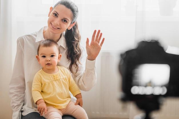 Lindo bebê criança com jovem mãe na frente da câmera vlogging ou blogging Foto Premium