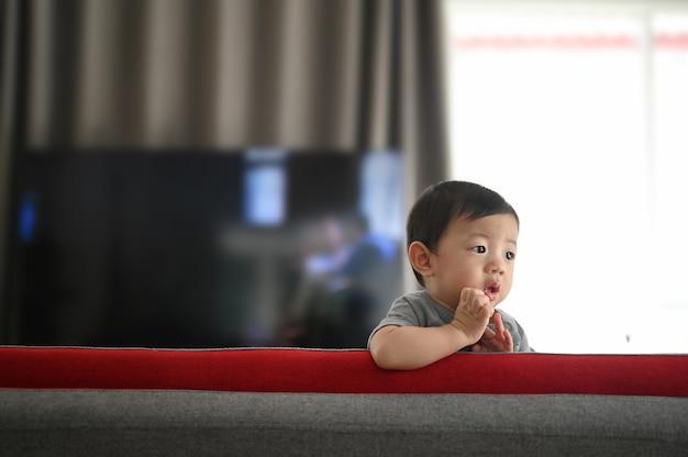 Lindo bebê de pé em um sofá na sala de estar em casa. Foto Premium