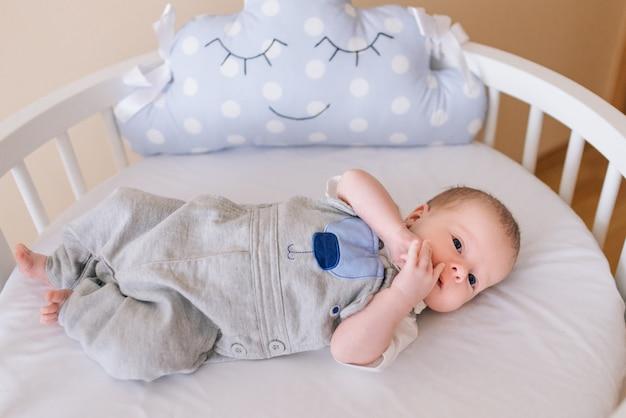 Lindo bebê recém-nascido, deitado em uma cama redonda com belos pára-choques em delicados tons de cinza, azuis e brancos Foto Premium