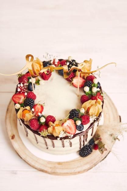 Lindo bolo de casamento com frutas, gotas de chocolate e com cartas de amor Foto gratuita