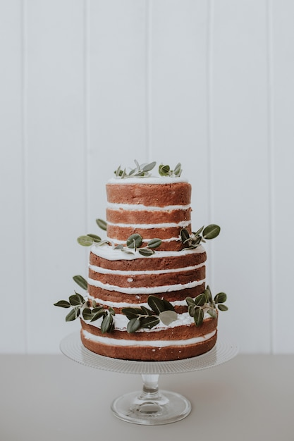 Lindo bolo de casamento rústico decorado com eucalipto em fundo branco de madeira Foto gratuita