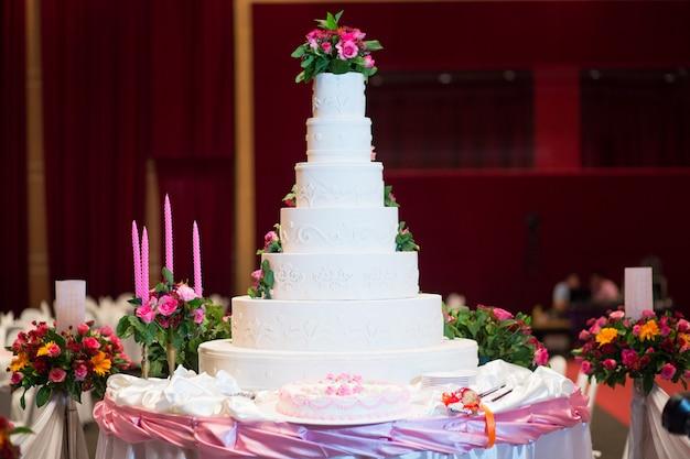 Lindo bolo decorar com rosa rosa, flor e vela para cerimônia de casamento Foto Premium
