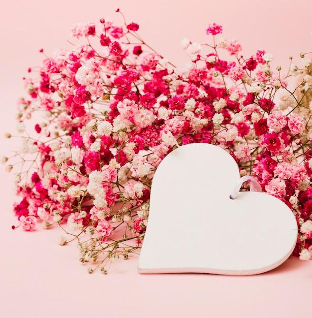 Lindo buquê de flores da respiração do bebê com forma de coração branco em fundo rosa Foto gratuita