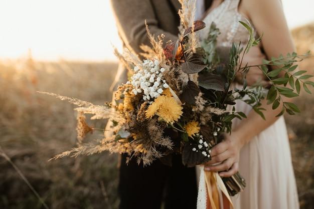 Lindo buquê de flores silvestres nas mãos da noiva Foto gratuita