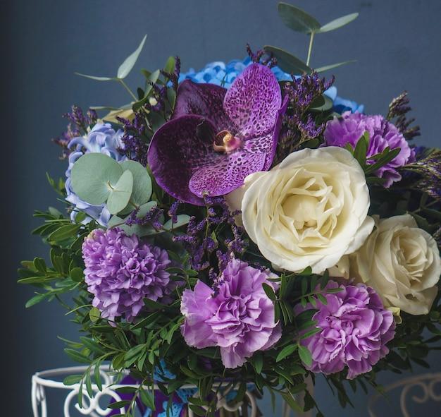 Lindo buquê de lilases e rosas em pé em um vaso portanto rústico Foto gratuita