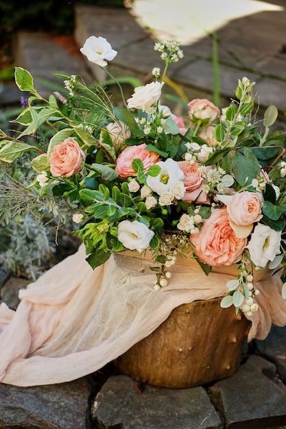 Lindo buquê em um toco de madeira. Rosas cor de rosa. Dia do casamento. Foto Premium