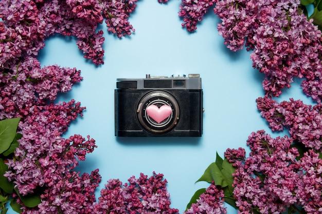 Lindo buquê lilás e câmera fotográfica retrô sobre um fundo azul Foto Premium