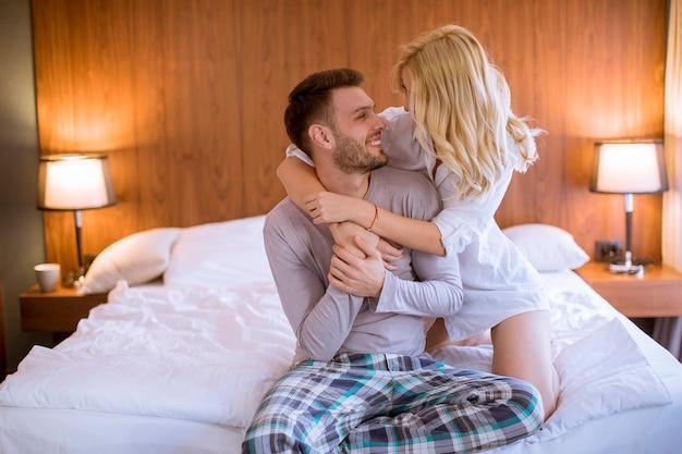 Lindo casal abraçando na sua cama em casa Foto Premium