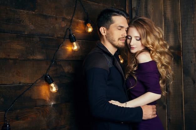 Lindo casal apaixonado abraços contra luzes Foto Premium