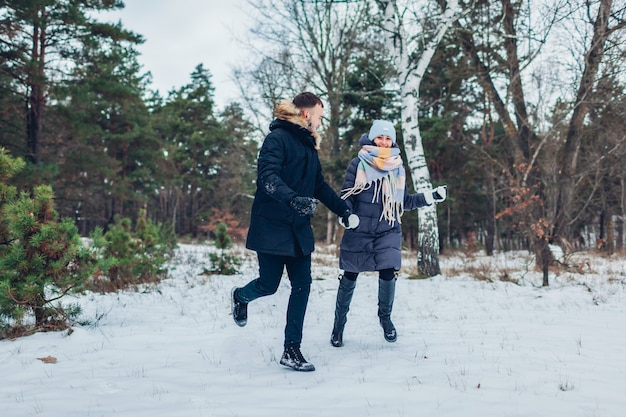Lindo casal apaixonado correndo juntos na floresta de inverno. pessoas se divertindo ao ar livre Foto Premium