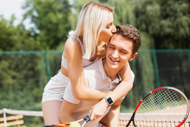 Lindo casal ativo na quadra de tênis Foto gratuita