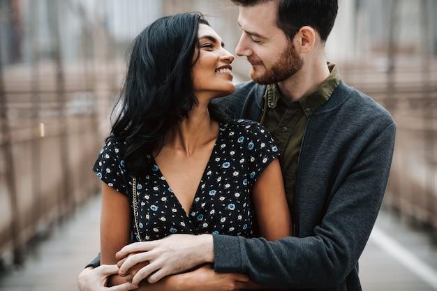Lindo casal de homem americano com barba e concurso mulher oriental abraçar um ao outro Foto gratuita