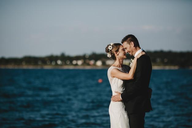 Lindo casal de noivos abraça outro pé concurso na margem do lago Foto gratuita