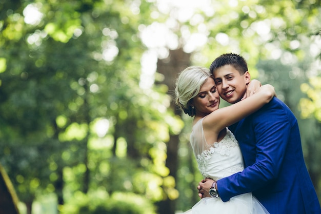 Lindo casal de noivos abraçando no parque Foto gratuita