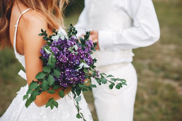 Lindo casal de noivos em um campo de verão Foto gratuita