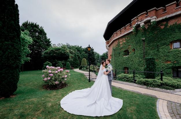 Lindo casal de noivos está de pé no parque verde perto do edifício totalmente coberto de folhas Foto gratuita