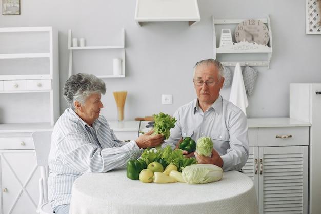 Lindo casal de velhos prepara comida na cozinha Foto gratuita