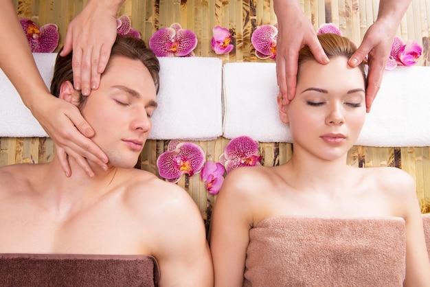 Lindo casal deitado em um salão de spa, desfrutando de uma massagem na cabeça juntos. Foto gratuita