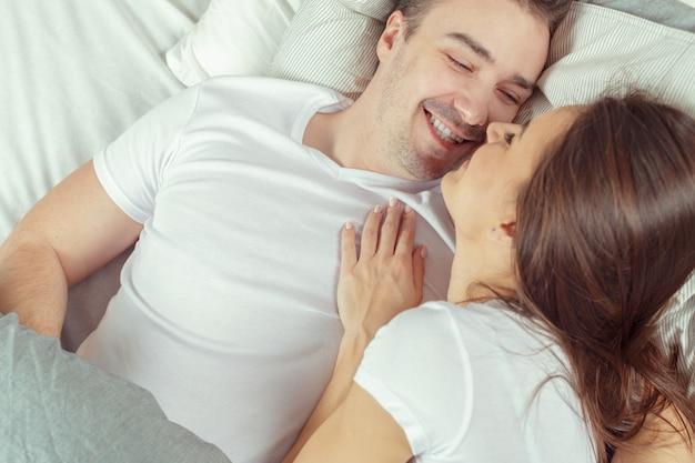 Lindo casal deitado juntos na cama Foto Premium