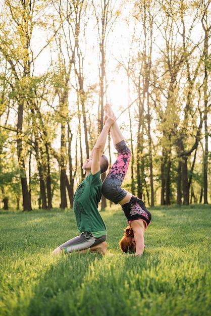 Lindo casal fazendo acro yoga na grama Foto gratuita