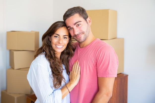 Lindo casal hispânico feliz parado entre caixas de papelão em seu novo apartamento, se abraçando e olhando para a câmera Foto gratuita