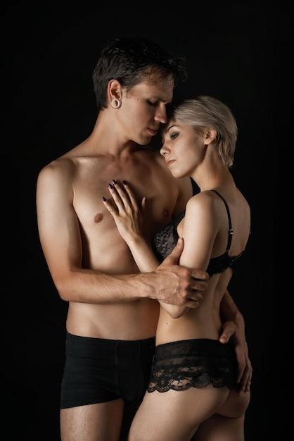 Lindo casal homem e mulher em roupa interior, abraçando o relacionamento Foto Premium