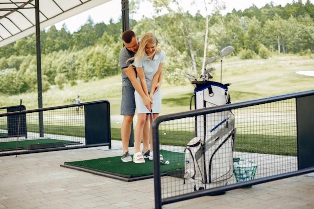 Lindo casal jogando golfe em um campo de golfe Foto gratuita