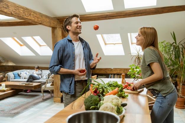Lindo casal jovem alegre cozinhar jantar juntos Foto Premium