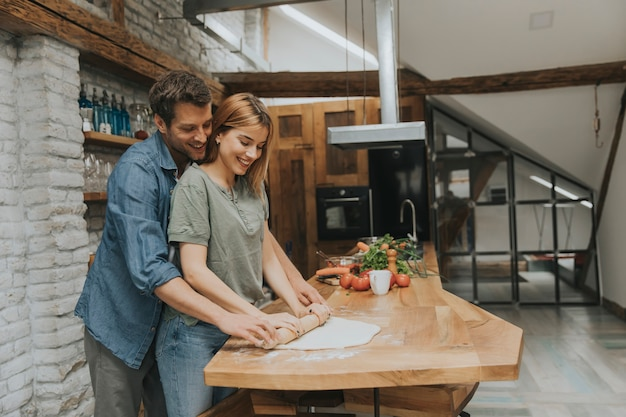 Lindo casal jovem alegre cozinhar o jantar juntos e se divertindo na cozinha rústica Foto Premium
