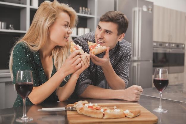 Lindo casal jovem comendo pizza juntos na cozinha Foto Premium