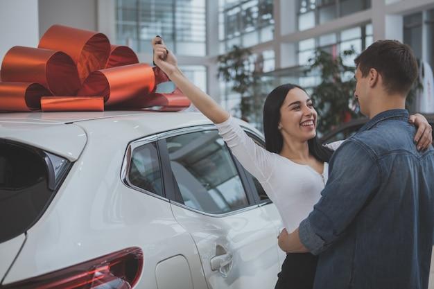 Lindo casal jovem comprando carro novo juntos Foto Premium