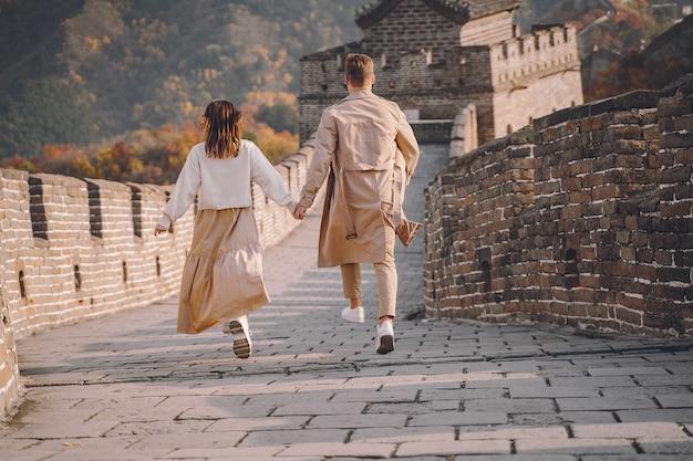 Lindo casal jovem correndo e pulando na grande muralha da china. Foto gratuita