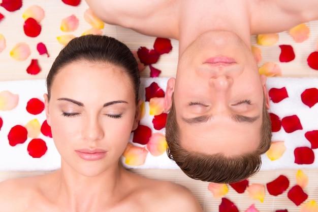 Lindo casal jovem relaxa deitado em pétalas de rosa. Foto gratuita