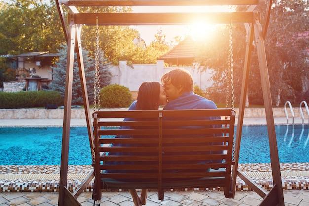 Lindo casal jovem sentado no banco à beira da piscina Foto gratuita