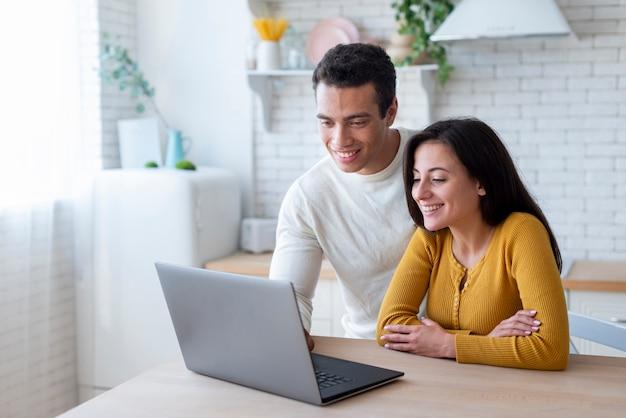 Lindo casal olhando para laptop Foto gratuita