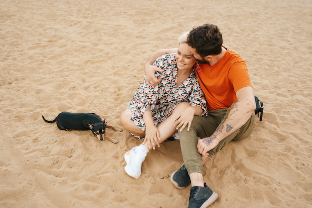 Casal e cachorro em praia