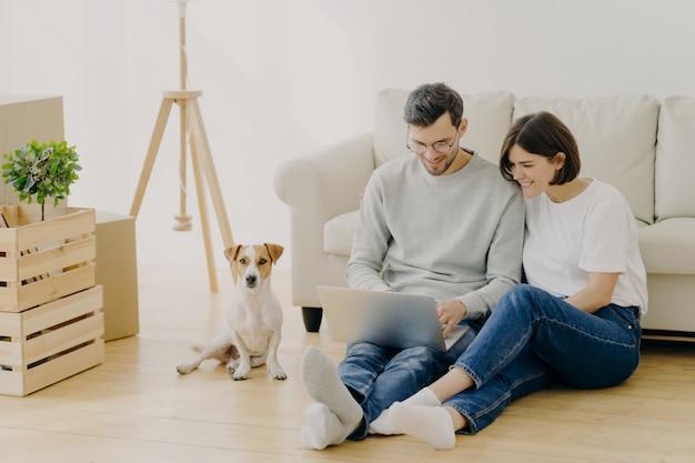 Lindo casal se muda para uma nova habitação, usa laptop moderno para pesquisar idéias de design para seu apartamento Foto Premium