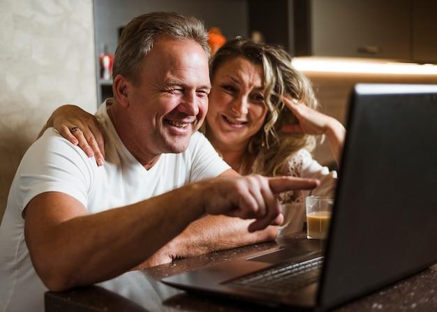 Lindo casal sênior rindo de laptop Foto gratuita