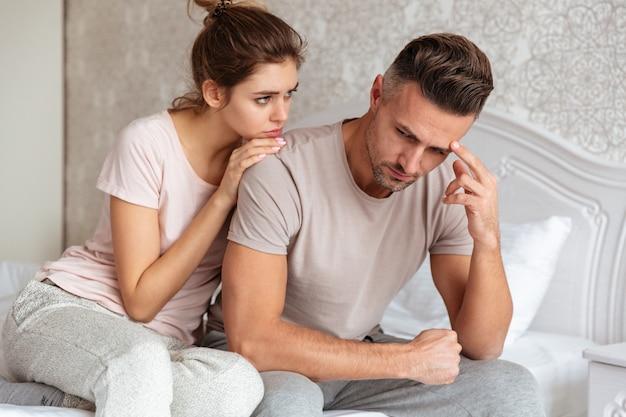 Lindo casal sentado na cama, enquanto a mulher acalmar o namorado que chateado Foto gratuita