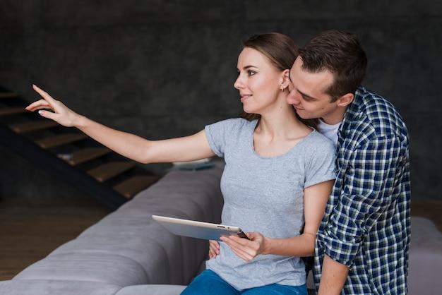 Lindo casal sentado no sofá com tablet Foto gratuita