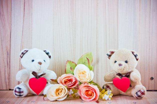 Lindo casal urso sente-se perto de rosas doces no chão Foto Premium