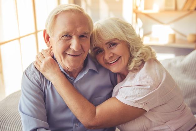 Lindo casal velho está abraçando, olhando para a câmera. Foto Premium