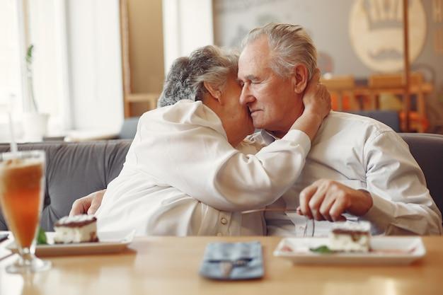 Lindo casal velho sentado em um café Foto gratuita