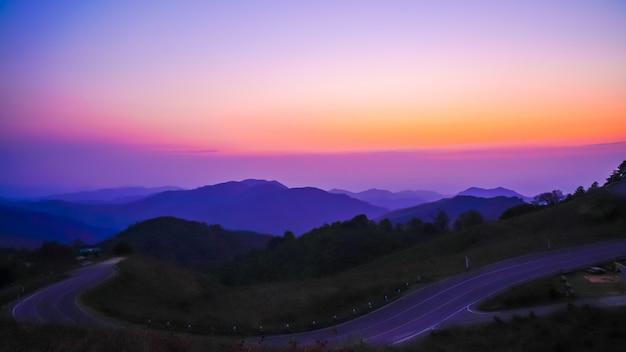 Lindo céu pôr do sol com montanha e estrada Foto Premium