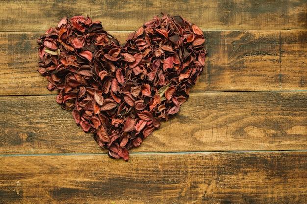Lindo coração marcado com pétalas secas Foto Premium